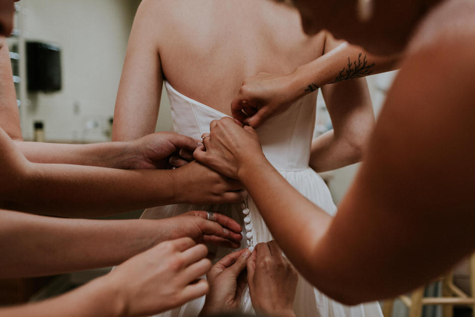 bridesmaids helping bride with dress, mostly just hands