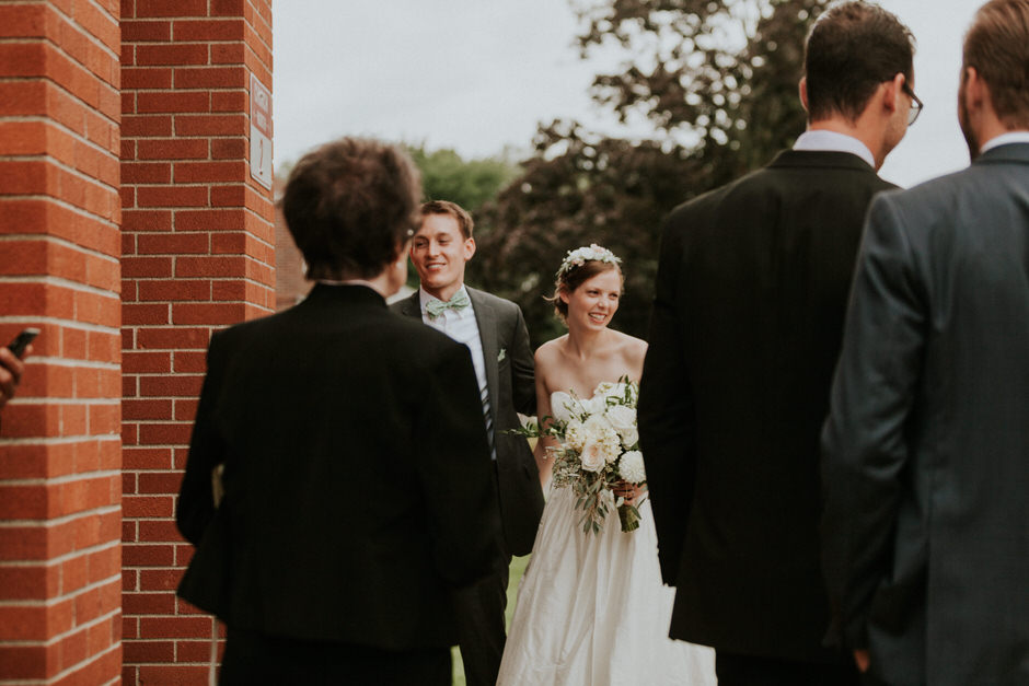 bride and groom greeting guests outside of church, laughing and smiling
