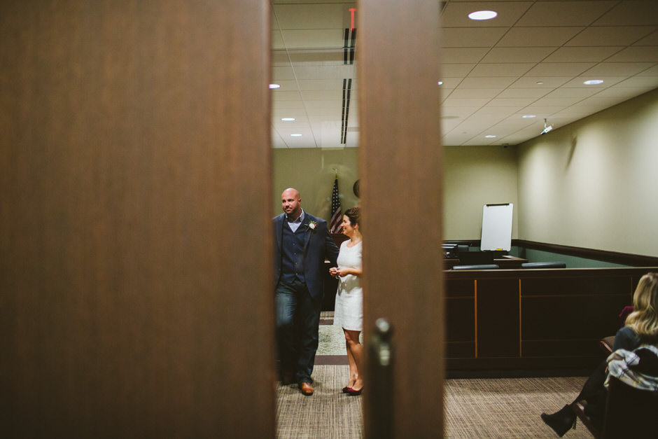 bride and groom through doors of grand haven courthouse