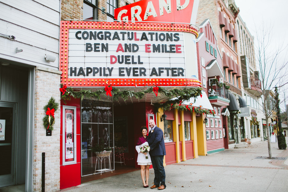 couple under the grand sign in grand haven mi