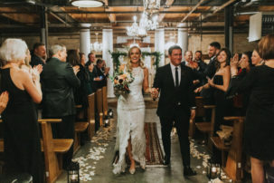 bride and groom walking down aisle together at salvage one-