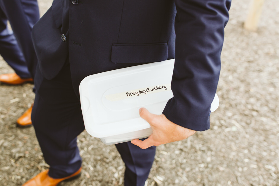 groom holding a box which says bring day of wedding