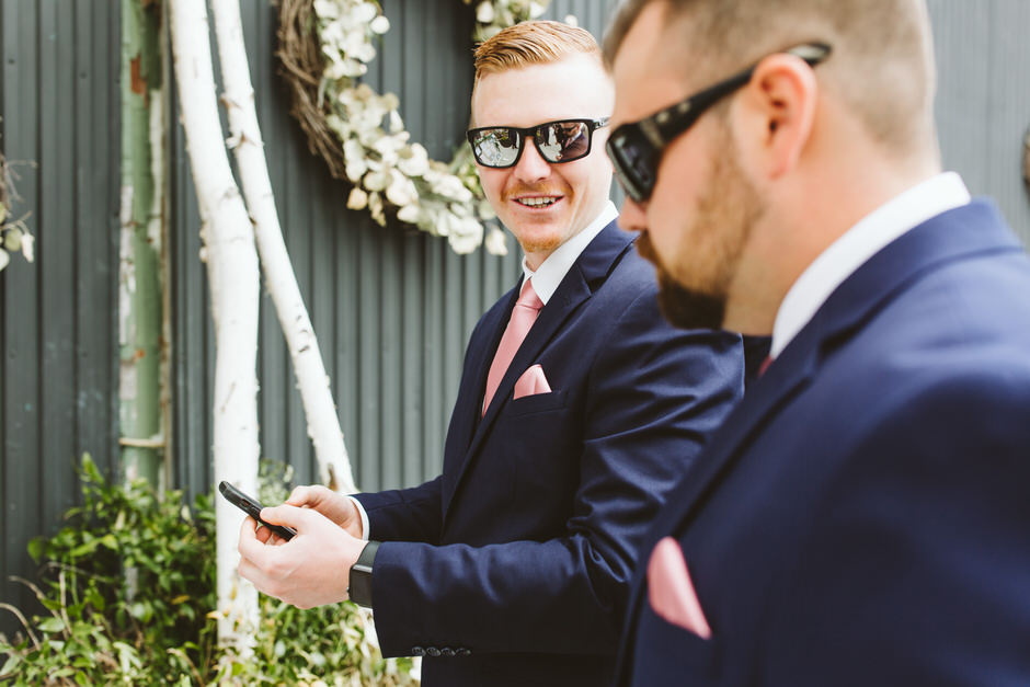 guy in blue suit with glasses showing something on his phone